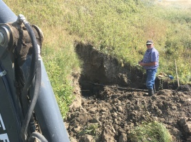 Installing a curb stop on the back side of a dam at Clark Creek Ranch.